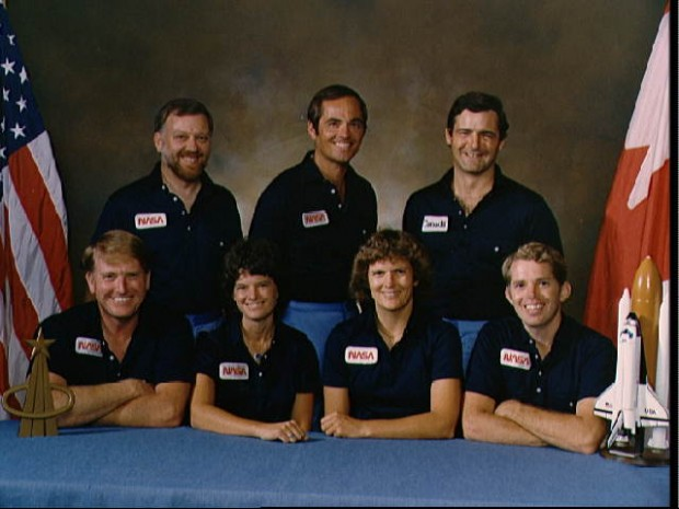 Official photo of the 41-G crew. They are (bottom row, left to right) Astronauts Jon A. McBride, pilot; and Sally K. Ride, Kathryn D. Sullivan and David C. Leestma, all mission specialists. Top row from left to right are Paul D. Scully-Power, payload specialist; Robert L. Crippen, crew commander; and Marc Garneau, Canadian payload specialist.