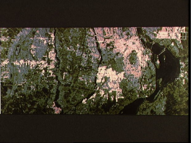 False-color image showing Montreal, Quebec, Canada, and was acquired by the Shuttle Imaging Radar-B (SIR-B) during STS 41-G. The St. lawrence River dominates the right portion of the photo. Several bridges cossing the river are visible. Pink and blue areas are generally buildings or pavement. Light green areas regions of natural vegetation; darker green areas are generally cultivated regions. A race track like structure is apparent at top left. The Riviere des Milles Illes and the Riviere des Prairies (left and right, respectively), join to form a U-shaped waterway at the center of the image. The large elliptical green-centered feature west of the St. Lawrence is Mt. Royal.