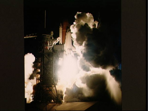 View of the early morning launch of STS 41-G Challenger. The dark launch complex is illuminated by spotlights as the orbiter begins its ascent from the pad. The light is reflected off the clouds of smoke from the orbiter's engines.