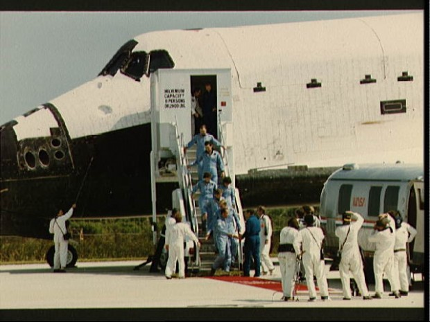 STS 41-G crew leaves the orbiter after landing at Kennedy Space Center at the end of their mission. Astronaut Robert Crippen shakes hands with George W.S. Abbey, Director of JSC's Flight Crew Operations, while the other crewmembers wait behind him. They are Jon McBride, David Leestma, Sally K. Ride, Kathryn Sullivan, Marc Garneau and Paul Scully-Power.