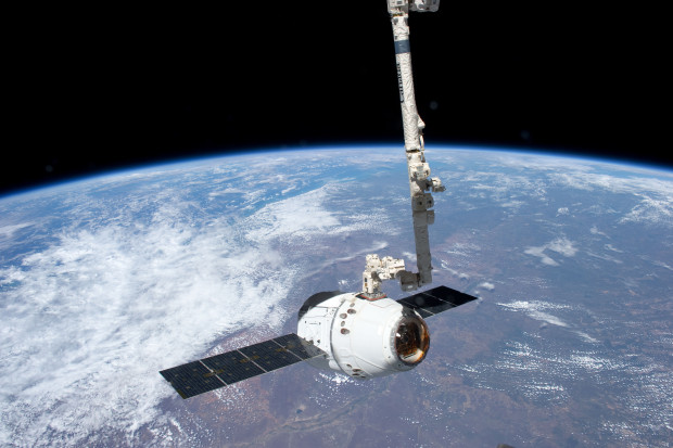 Canadarm2 catches a visiting SpaceX Dragon cargo capsule at the International Space Station. (Credit: NASA)