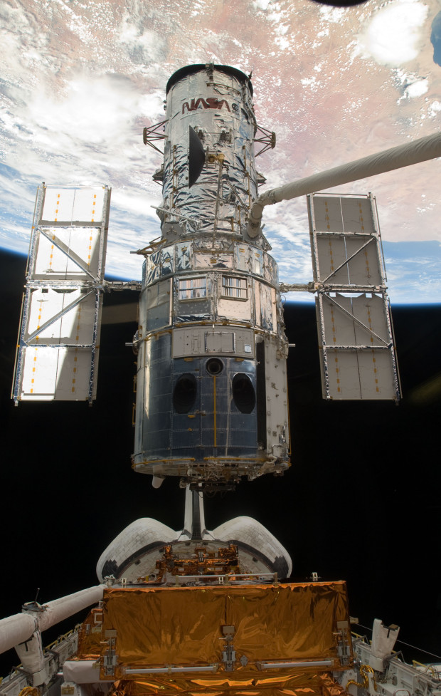 Canadarm lifts the Hubble Space Telescope out of the payload bay of Atlantis, moments before it is released into space following the successful repair mission of STS-125. (Credit: NASA)
